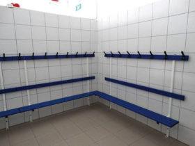 Locker room system installed against two white tiled walls