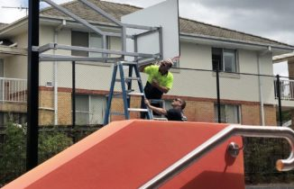 Two team members working on an outdoor basketball system