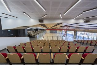Back of mezzanine seating overlooking a wooden court